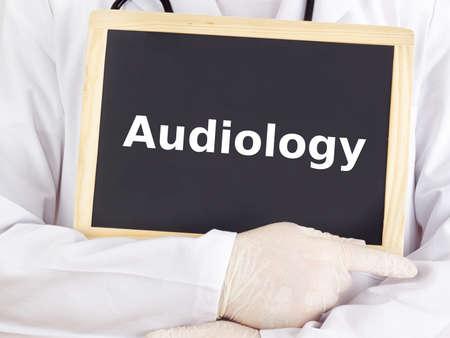 medico: Doctor shows information on blackboard: audiology