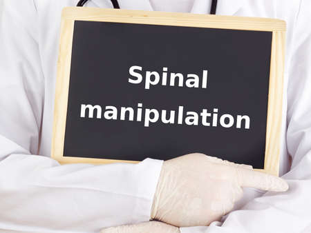spinal manipulation: Doctor shows information: spinal manipulation Stock Photo