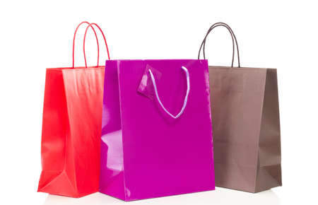 Three colorful shopping bags on white table Standard-Bild