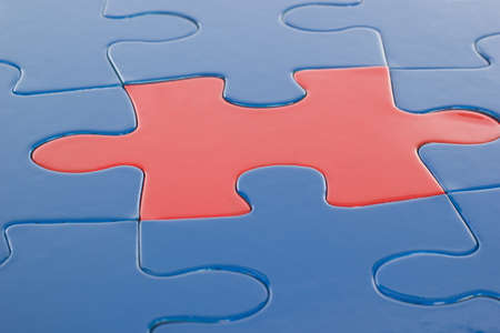 Single red piece in blue puzzle photo