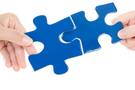 cohesiveness: People putting two pieces of jigsaw together Stock Photo