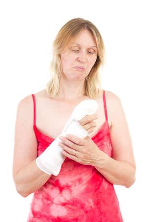 Mature woman looking sad at her bandaged finger