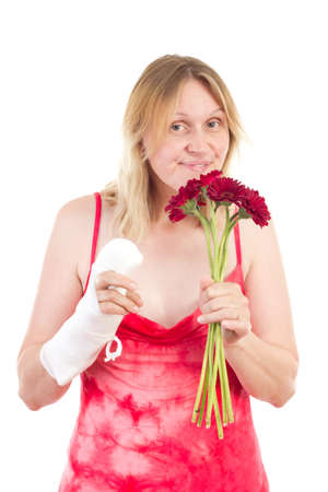 Woman with bandaged hand sniffs at flowers
