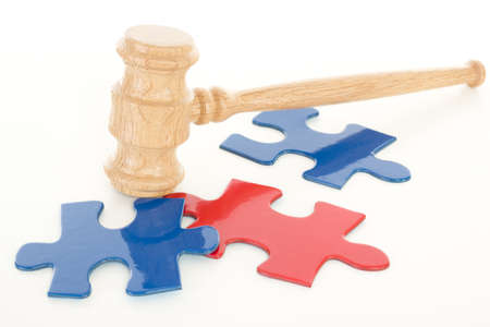 Wooden gavel hitting colourful puzzle pieces
