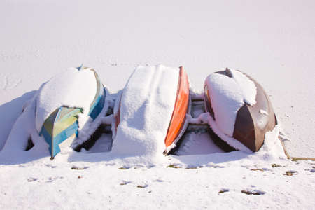 sub zero: Boats on frozen lake covered with snow