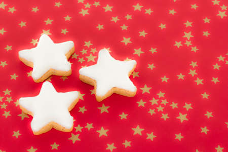 Shining star shaped cinnamon biscuits on red background with golden stars Stock Photo