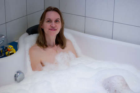 Having nice bath with lot of foam against stress Imagens
