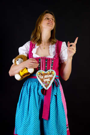 Woman in dirndl pointing at something photo