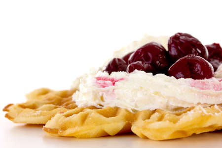 Close-up of waffle with whipped cream and cherries