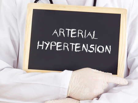 Doctor shows information: arterial hypertension Stock Photo
