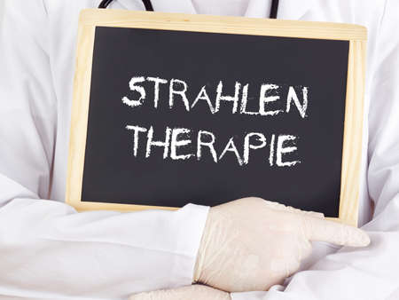 radiation therapy: Doctor shows information: radiation therapy in german language Stock Photo