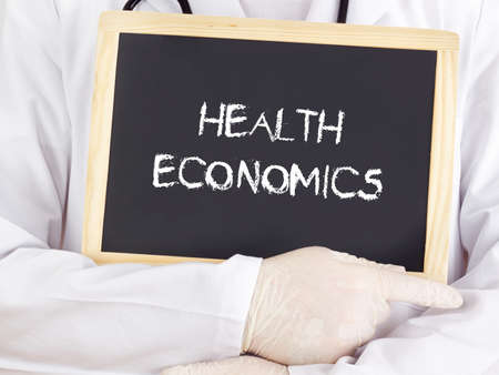 Doctor shows information on blackboard: health economics Standard-Bild
