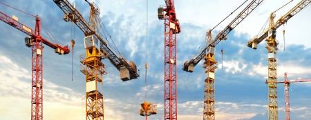 hoist: cranes on building site in panoramic image