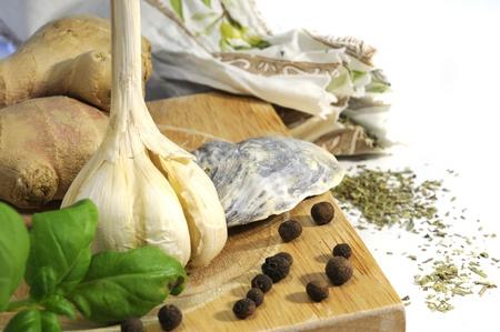 garlic, ginger and allspice on wooden desk