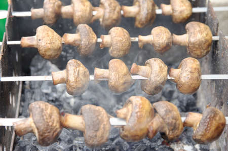 brazier: Brown juicy mushrooms cooked on the brazier. Stock Photo