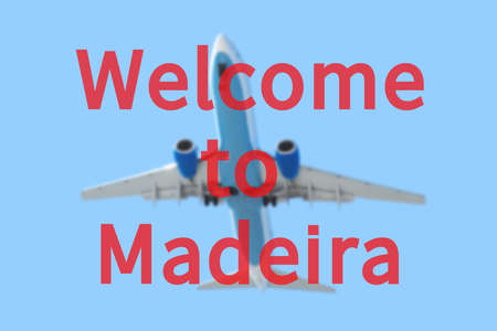 Blurred background with passenger airplane. Inscription Welcome to Madeira on the sky. Stock Photo