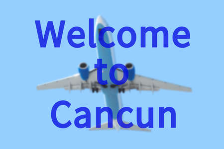 cancun: Blurred background with passenger airplane. Inscription Welcome to Cancun on the sky. Stock Photo