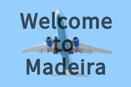 madeira: Blurred background with passenger airplane. Inscription Welcome to Madeira on the sky. Stock Photo