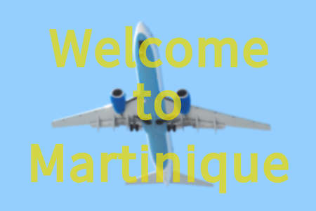 martinique: Blurred background with passenger airplane. Inscription Welcome to Martinique on the sky.