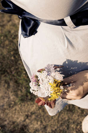 bow belly: Young pregnant woman with a bunch of wild flowers. Selective focus. Stock Photo