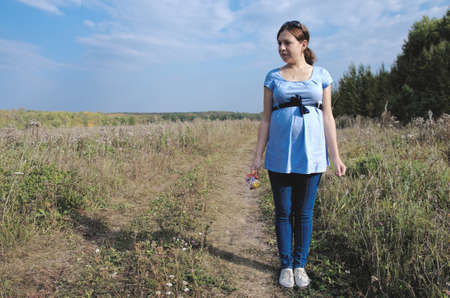 earth road: Young pregnant woman in field with a bunch of wild flowers on the earth road.