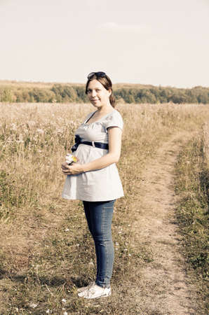 earth road: Young pregnant woman in field with a bunch of wild flowers on the earth road. Sepia toned.
