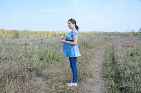 earth road: Young pregnant woman in field with a bunch of wild flowers on the earth road. Selective focus.