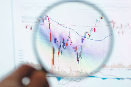 technical analysis: Online Stock Trading Platform with stock charts through a magnifying glass. Technical analysis.