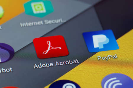 application icons: SARANSK, RUSSIA - JUNE 04, 2016: A smartphone screen shows Adobe Acrobat icon on the screen. Selective focus.