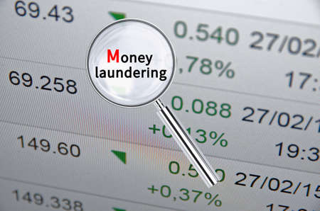 Magnifying lens over background with text Money laundering, with financial data visible in the background. 3D rendering.