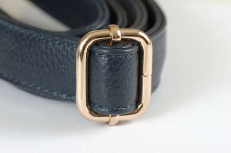 Strap with golden plated buckle on white background.
