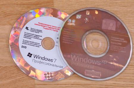 SARANSK, RUSSIA - MAY 24, 2017: Windows 7 DVD and Windows XP CD on wooden background.