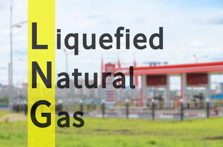 Acronym LNG as Liquefied natural gas. Out-of-focus background - Fueling station.