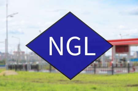 Blue diamond symbol with acronym NGL. Out-of-focus background - Fueling station.