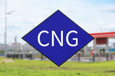 Blue diamond symbol with acronym CNG. Out-of-focus background - Fueling station.
