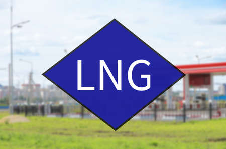 Blue diamond symbol with acronym LNG. Out-of-focus background - Fueling station. Stock Photo
