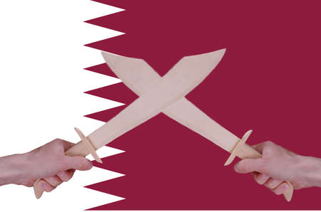 sabre's: Hands hold crossed wooden sabres, Qatar flag visible on the background.
