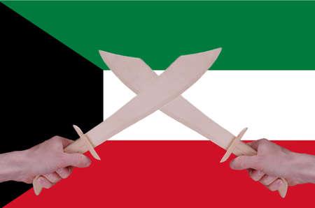 sabre's: Hands hold crossed wooden sabres, Kuwait flag visible on the background.