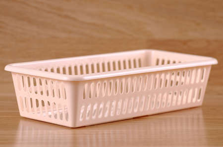 A plastic basket on a wooden table.