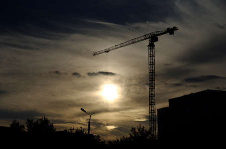 Tower crane against sunset. Overheating economics concept.