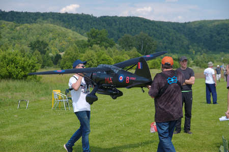 PENZA OBLAST, RUSSIA - JULY 15, 2017: Two man carry radio control flying model of a Westland Lysander aircraft. The Russian Aeromodelling Cup in Bolshoy Vyas village.