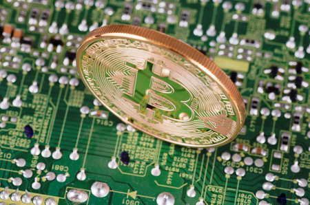 Golden plated bitcoin on a printed circuit board. Фото со стока