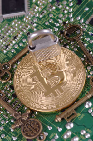Golden plated bitcoin with keys and padlock on a printed circuit board.