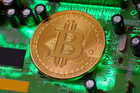 Golden plated Bitcoin on printed circuit board. Stock Photo