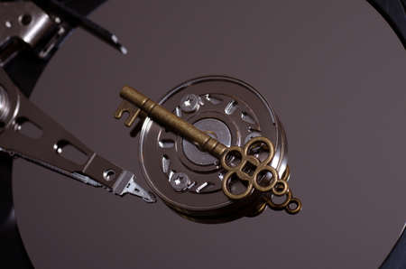 Data security concept. Bronze key on spindle of a hard disk drive. Stock Photo