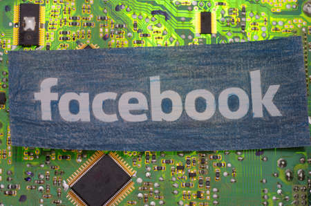 SARANSK, RUSSIA - MARCH 21, 2018: The Facebook icon printed on a paper and placed at circuit board. Editorial