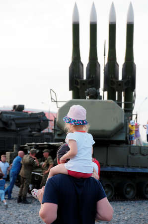 SARANSK, RUSSIA - JUNE 30, 2018: Father and child, Buk missile system visible on the background.