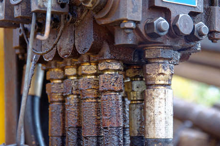A close-up of pipe system of hydraulic valves in industrial machinery.