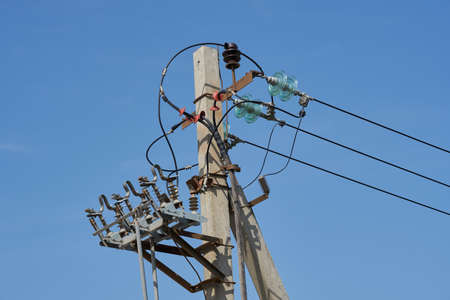 Concrete utility pole supporting wires for electrical power distribution.