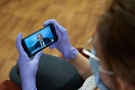 SARANSK, RUSSIA - APRIL 18, 2020: A woman in disposable gloves and a medical mask is watching the broadcast of the briefing The Centers for Disease Control and Prevention Chief Robert R. Redfield.